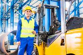 stock photo of forklift driver  - Forklift driver standing proud in manufacturing plant - JPG