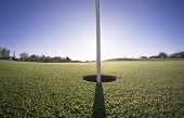 Wide angle close up photo of golf course putting green and flag with sun low on horizon.