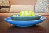 apples in a bowl on a wooden table in a living room