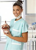 Attractive young dental assistant smiling happy, holding dentures in hand.