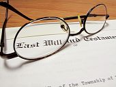 stock photo of deceased  - Actual last will and testament with eyeglasses on wooden desk - JPG