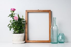 image of rose flower  - Vintage blank wooden frame bottles and rose in a pot on a white wall - JPG