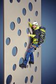 pic of climb up  - smiley man in equipment holding on climbing wall and showing thumbs up over blue background - JPG