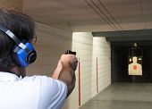 stock photo of shooting-range  - man shooting a handgun at a gun range - JPG
