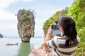 stock photo of james bond island  - Women tourist he is shooting a beautiful scenic view by mobile phone at Khao Tapu or James Bond Island in Ao Phang Nga Bay National Park Thailand - JPG