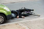 stock photo of accident emergency  - Unconscious Male Cyclist Lying On Road After Road Accident - JPG