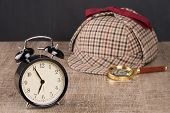 picture of private investigator  - Deerstalker Hat and magnifying glass on Old Wooden table - JPG