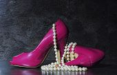 stock photo of black heel  - Glamorous pair of ladies pink high heels with long strand of white pearls against a dramatic black slate background still life - JPG