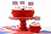 stock photo of jacking  - Red white and blue theme cupcakes on red cake stand with UK Union Jack flags on white wood table for Queens Birthday and Great Britain party food - JPG