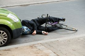 picture of accident victim  - Unconscious Male Cyclist Lying On Road After Road Accident - JPG