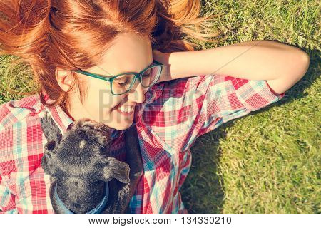 poster of Little Dog and His Happy Owner Having Fun and Lying on Green Grass. Happy Girl and Shih Tzu Dog. Pets Love and Playing Concept. Toned Photo with Copy Space.