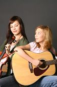 stock photo of musical instrument string  - two teenage sisters with violin and guitar against dark background - JPG