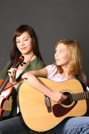 foto of musical instrument string  - two teenage sisters with violin and guitar against dark background - JPG