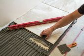 Ceramic Tiles And Tools For Tiler. Worker Hand Installing Floor Tiles. Home Improvement, Renovation  poster