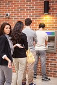 Portrait of an impatient woman queuing at an ATM