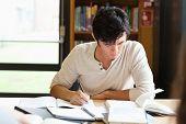 Estudiante masculino, trabajando en un ensayo en una biblioteca