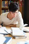 Retrato de un estudiante serio escribir un ensayo en una biblioteca