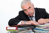Man leaning on piles of paperwork