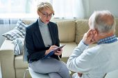 Portrait Of Blonde Female Psychologist Talking To Senior Man During Consultation, Copy Space poster