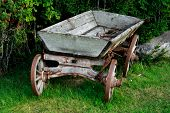 stock photo of ox wagon  - Old and used wagon standing near green bushes - JPG