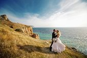 Kissing wedding couple staying over beautiful landscape