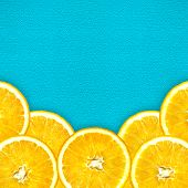 Juicy Cut Oranges On A Bright Blue Background. Oranges Are Located At The Bottom Of The Photo In A S poster