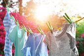 Rope with clean clothes outdoors on laundry day poster