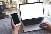 Mockup Image Of Hands Holding Blank Mobile Phone While Using Laptop With Blank White Desktop Screen  poster