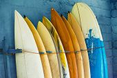 Set Of Different Color Surf Boards In A Stack By Ocean.bali, Indonesia. Surf Boards On Sandy Weligam poster