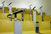 Closeup microphone in holder in auditorim with yellow chairs and microphones. poster