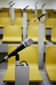 Closeup microphone in holder in auditorim with yellow chairs and microphones, shallow dof. poster