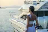 Young Beautiful Brunette Woman Relaxing At Dock Near Boat, Sunset On Summer Day. Woman In Fashionabl poster