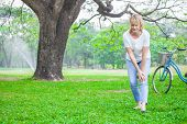 Senior Woman Walking In Autumn Park And Having Knee Pain. Arthritis Pain Concept. poster