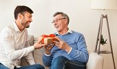 Mature Son Congratulating Elderly Father Giving Him Birthday Gift Sitting On Sofa At Home. Selective poster