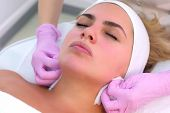 Portrait Of Woman Client On Facial Cleansing Procedure That Washes Hands Of Beautician. Cosmetologis poster