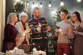 Cheerful adults with sparkling bengal lights chatting at Christmas party at home with decorated firt poster