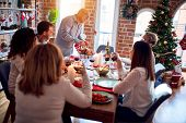 Family and friends dining at home celebrating christmas eve with traditional food and decoration, pr poster