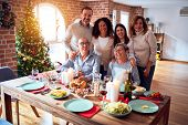 Family and friends dining at home celebrating christmas eve with traditional food and decoration, ta poster