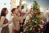 Young man with his little daughter decorating Christmas tree at home among other family members whil poster