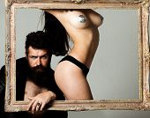 Sexy Hot Girl With Covered Nipples Standing In A Frame. Handsome Hipster Bearded Man Holding Frame W poster