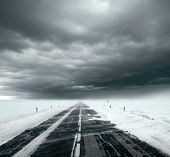 Beautiful stormy sky with clouds and snow road. Snow road in the middle of snow fields poster