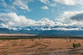Panorama Of To The Village Landscape On Background Snow-capped Mountain Peaks. View Mountain In With poster