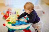 Adorable Cute Beautiful Little Baby Girl Playing With Educational Sorter Toys At Home Or Nursery. He poster
