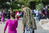 hair on the braids of a girl on the street. blond long hair braided in street photography. poster