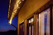 Cozy Scene Of String Lights Hanging Under The Roof At Evening Time. Fashion Decoration With Bulbs Fo poster