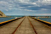 Railway Tracks Down The Middle Of Tokomaru Bay Wharf From A Vanishing Point Perspective poster