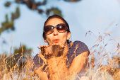 Woman Blow Grass Seeds From Hand In Meadow. Healthy People Lifestyle. Woman Blow Grass Seeds From Ha poster