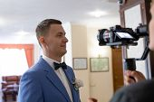 Videography Of The Wedding Ceremony With The Groom In A Blue Suit Using The Camera, Operator And Sta poster