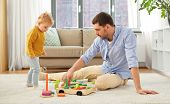 family, fatherhood and people concept - happy father and little baby daughter playing with wooden to poster