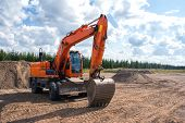 Orange Construction Wheeled Excavator At A Construction Site. poster